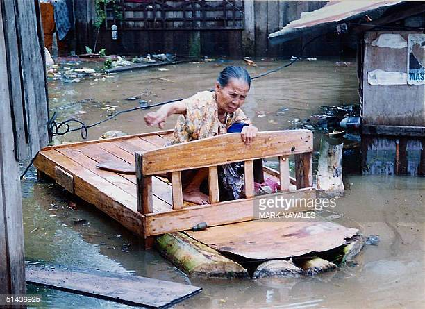 An elderly woman rides a floating bed outside her flooded house in Sultan Kudarat southern island of Mindanao, 07 October 2004. Rio Grande river...