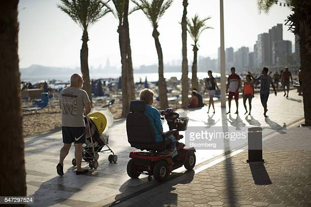 An elderly woman rides a mobility scooter along the beachfront promenade in Benidorm Spain on Tuesday July 12 2016 Spain registered record tourism...