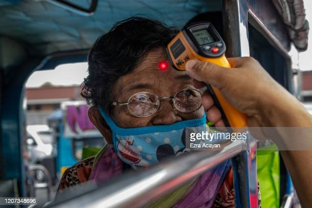 An elderly woman riding a passenger jeepney has her temperature checked at a checkpoint as authorities begin implementing lockdown measures on March...