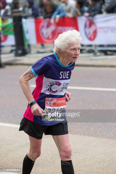 An elderly woman running for Cancer Research UK charity at Birdcage Walk during The Virgin London Marathon on 28th April 2019 in London in the United...