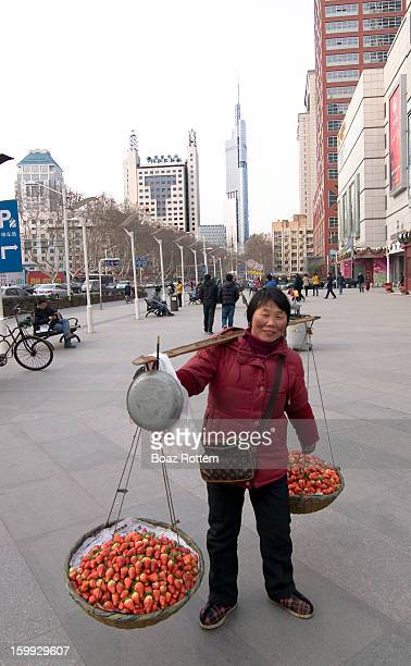 CONTENT] An elderly woman selling strawberries in the middle of Nanjing's business center Zifeng tower in the background
