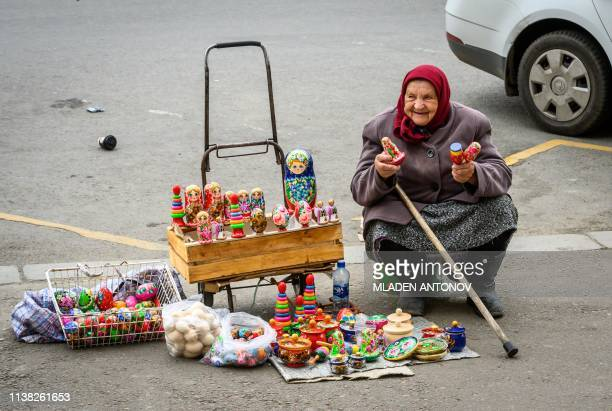 An elderly woman sells Easter eggs and Russian souvenirs on a street in central Moscow on April 20, 2019. - Orthodox Christians celebrate Easter on...