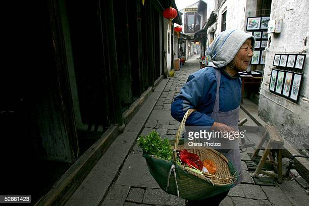 An elderly woman sells vegetables on April 15, 2005 in Zhouzhuang Town of Kunshan City, Jiangsu Province, China. Zhouzhuang, one of the most famous...