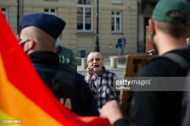 An elderly woman shows his middle finger to a man holding a sign and LGBT flag during a pro-life demonstration on September 20, 2020 in Warsaw,...