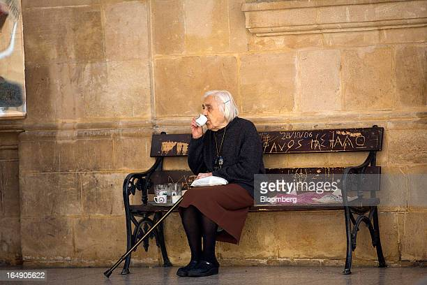 An elderly woman sits and drinks coffee on a bench in a churchyard in Nicosia Cyprus on Friday March 29 2013 Cypriots face a second day of bank...