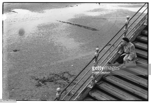 An elderly woman sits daydreaming on a flight of beachside steps