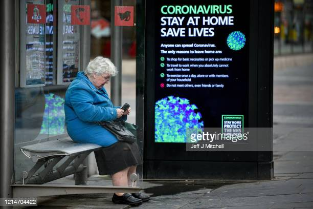 An elderly woman sits in a bus stop on Argyll Street as people are asked to socially distance themselves amid the coronavirus outbreak on March 25,...