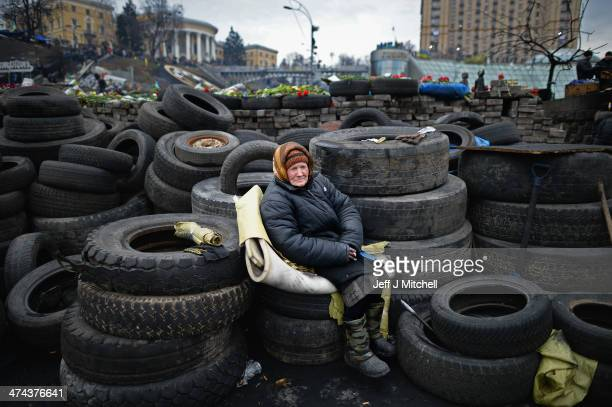 An elderly woman sits on tyres at a barricade in independence square on February 23 2014 in Kiev Ukraine Prime Minister Yanukovych is said to have...