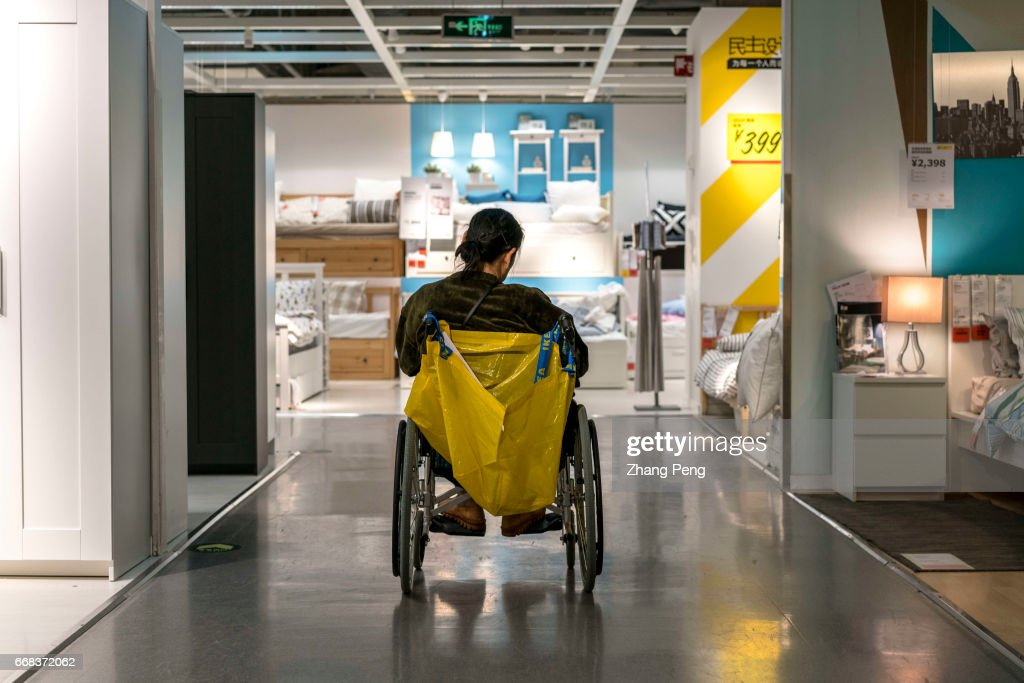 Good An Elderly Woman Sits On Wheelchair Waiting For Her Daughter, Who Buys  Furniture In The