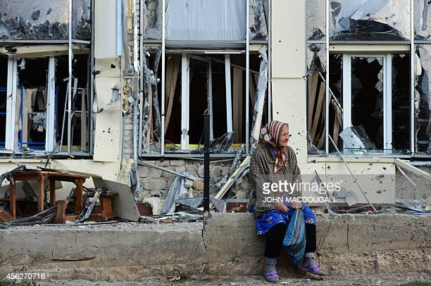 An elderly woman sits outside a damaged building in Pervomaisk some 50 kms west of Lugansk on September 28 2014 The town still held by rebels loyal...