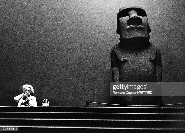 An elderly woman sits reading by a large stone statue or moai from Easter Island on display at the British Museum London 1967