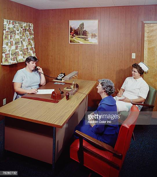 An elderly woman sits with a nurse in a woodpanelled office at the Van Rensselaer Manor Nursing Home while another staff member makes a telephone...
