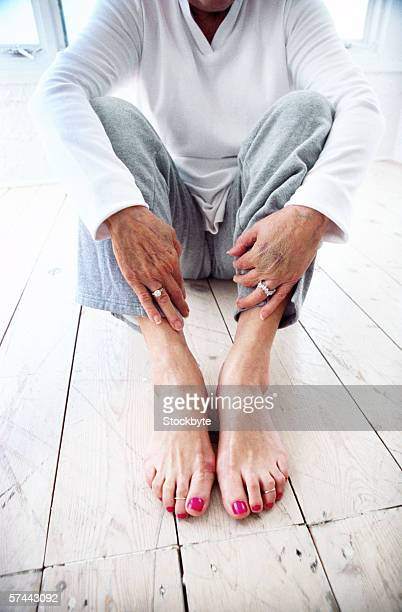 an elderly woman sitting on the floor - old lady feet stock pictures, royalty-free photos & images