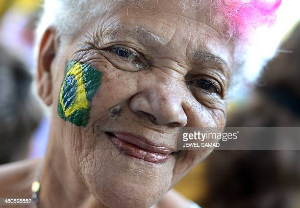 An elderly woman smiles after getting a Brazilian national flag painted on her cheek by a volunteer as she arrives to attend a Nigeria's national...