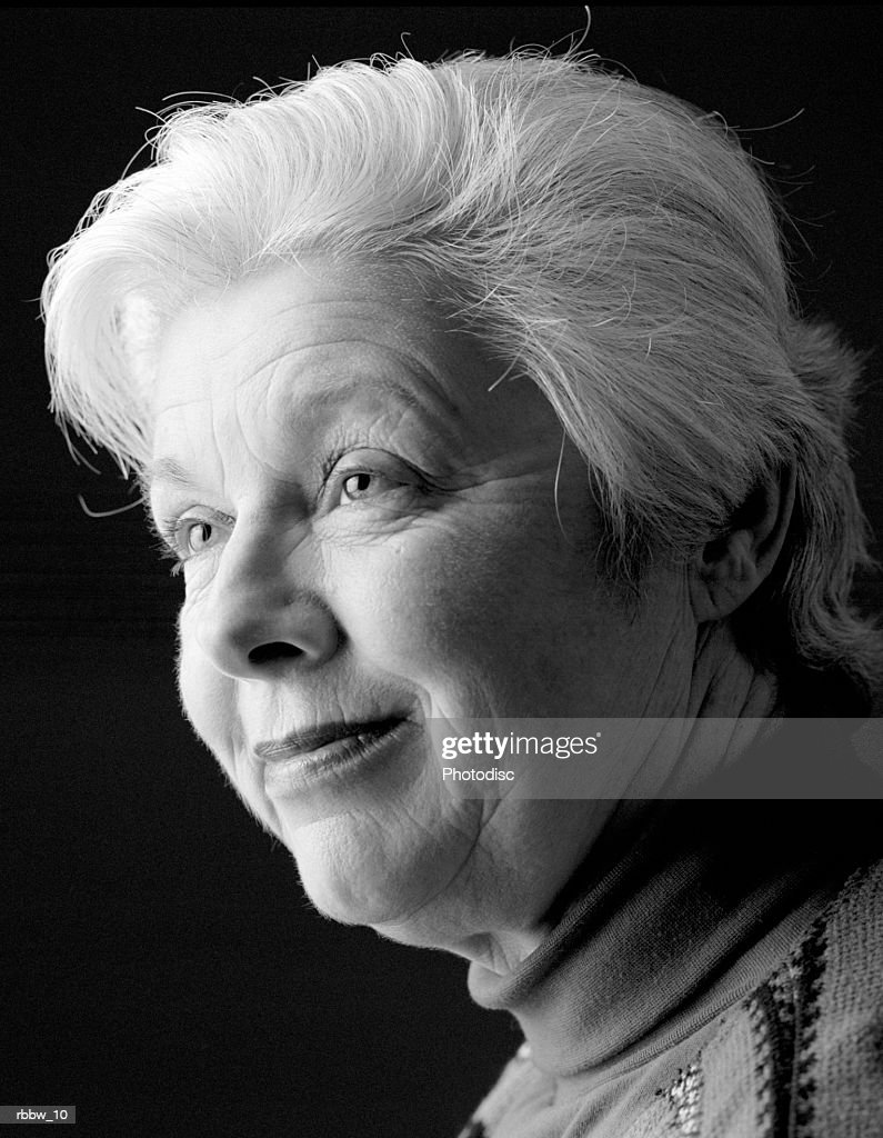 An elderly woman smiles to the side : Stockfoto