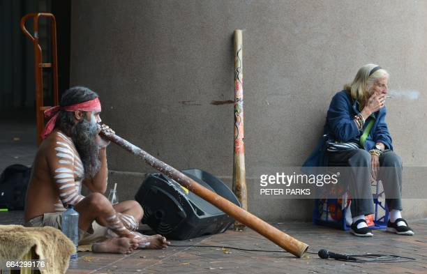 TOPSHOT An elderly woman smokes a cigarette whilst an Aboriginal man plays a didgeridoo in Circular Quay in Sydney on April 4 2017 / AFP PHOTO /...