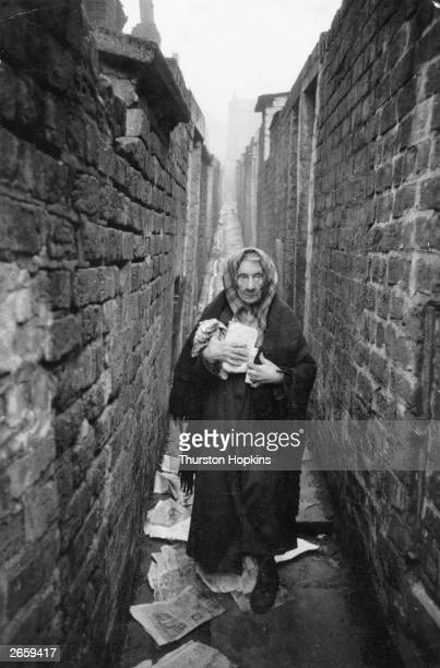 An elderly woman standing amongst the litter in a back alley of the Liverpool slums Original Publication Picture Post 8995 Liverpool Slums unpub