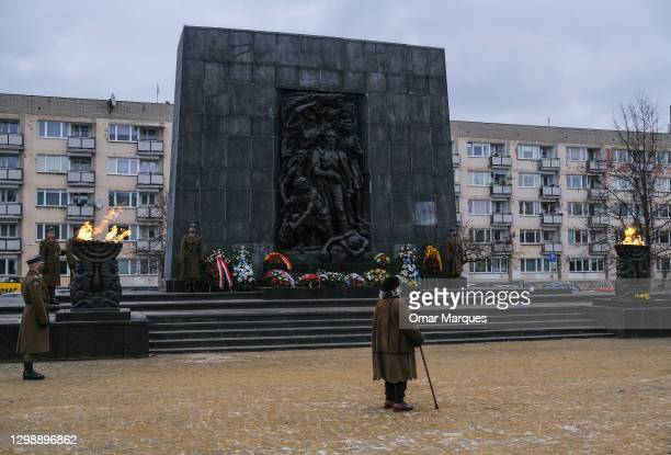 An elderly woman stands by the the Monument to the Ghetto Heroes during the Holocaust Remembrance Day on January 27, 2021 in Warsaw, Poland. January...
