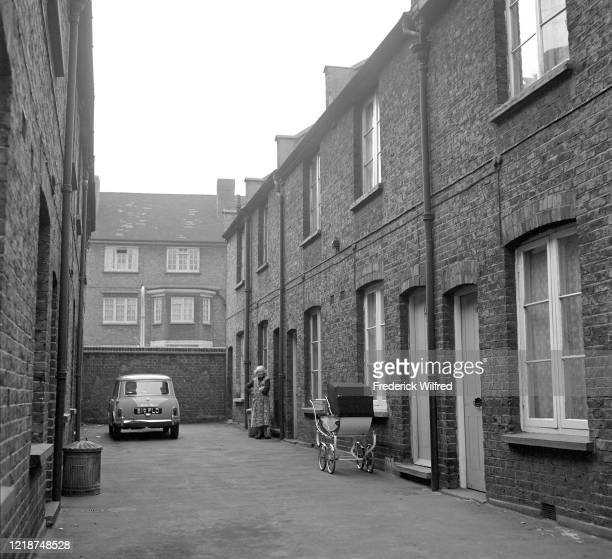 An elderly woman stands in front of a terraced house on a dead end alley London circa 1960 on the same alley a parked car and and a pram