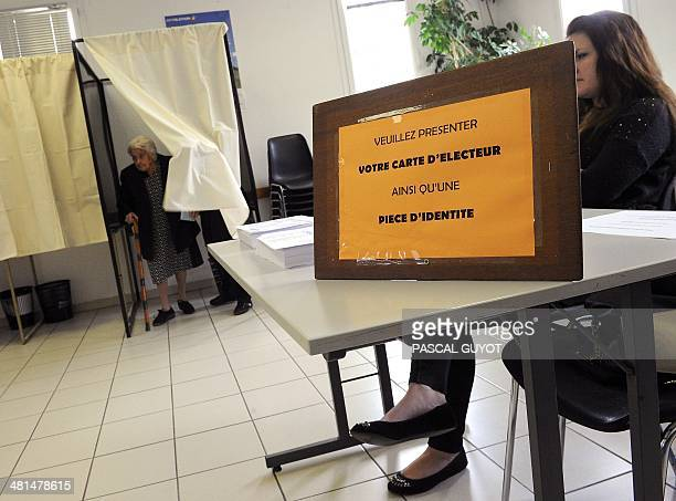 An elderly woman steps out of a polling booth before casting her ballot in the second round of the French municipal elections on March 30 2014 at a...