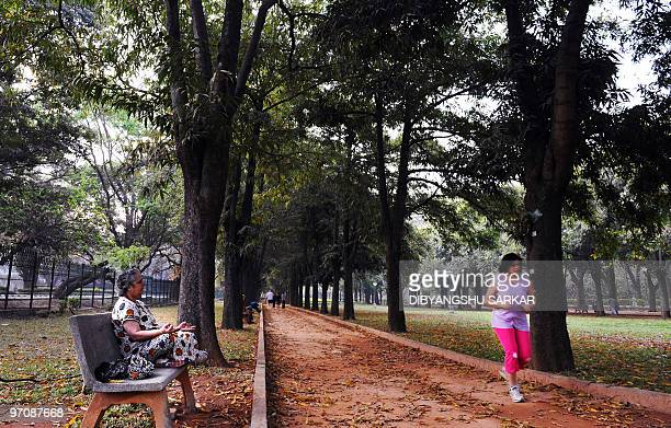 An elderly woman strikes a yoga pose on a bench as joggers runs past her in Cubbon Park in Bangalore on February 26 2010 The centrally located 300...