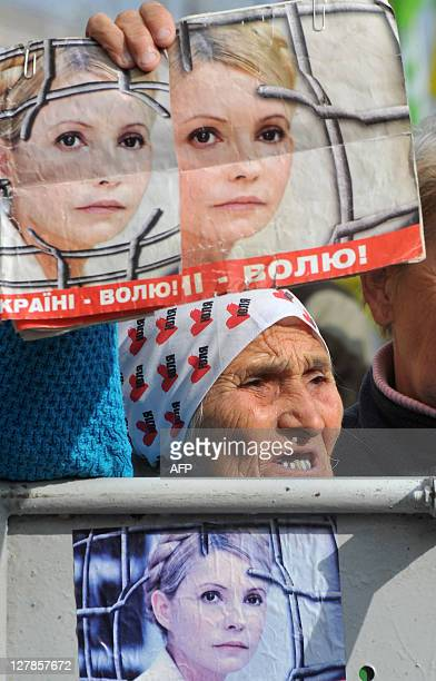 An elderly woman supporter of the former Prime Minister of Ukraine Yulia Tymoshenko holds placards with her portraits during a protest in front of...