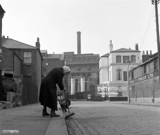 An elderly woman sweeping a road in London UK circa 1960