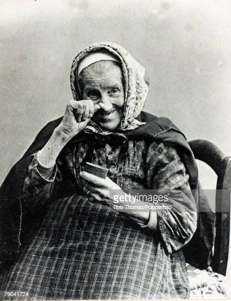 Early postcard France Old woman with a tin of snuff which she puts up her nose circa 1900