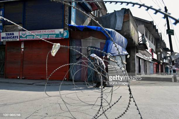An elderly woman tries to cross concertina wire that was erected by the Indian troopers during restrictions in Srinagar Indian administered Kashmir...