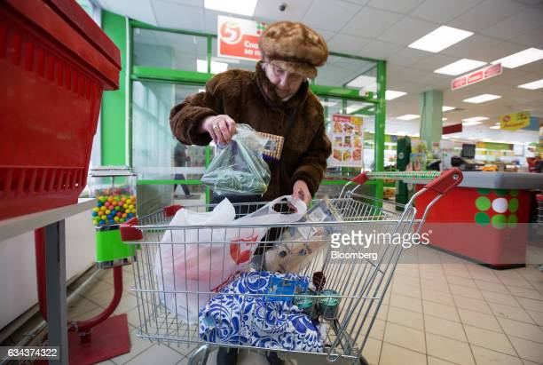 An elderly woman unloads her shopping cart into a plastic bag after paying for her goods inside a Pyaterochka supermarket operated by X5 Retail Group...