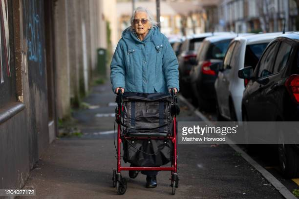 An elderly woman uses a walking aid on a residential street on December 9, 2019 in Port Talbot, United Kingdom.