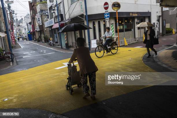 An elderly woman uses a wheeled walking frame as she walks through a shopping district in Kadoma, Osaka Prefecture, Japan, on Friday, June 8, 2018....