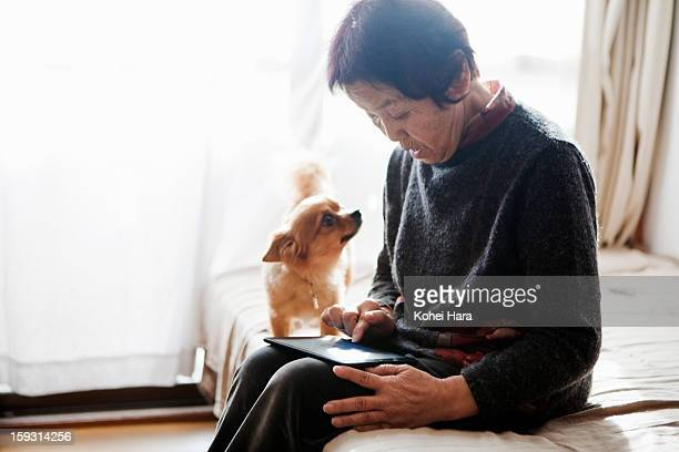 an elderly woman using a digital tablet