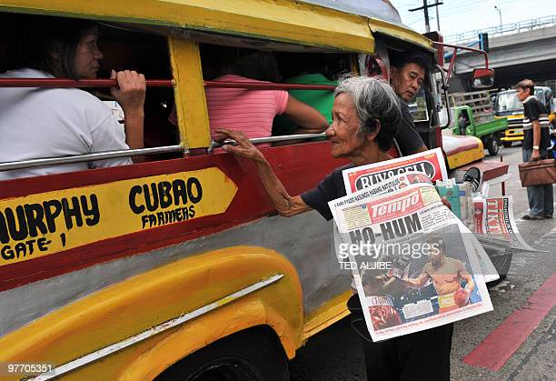 An elderly woman vendor sells newspapers with headlines of the welterweight bout between Philippines boxing superstar Manny Pacquiao and Joshua...