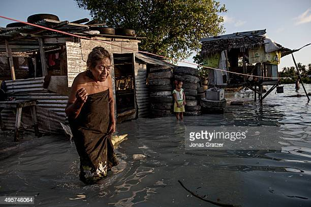 An elderly woman wades through kneehigh sea water that flooded her house and village The people of Kiribati are under pressure to relocate due to sea...