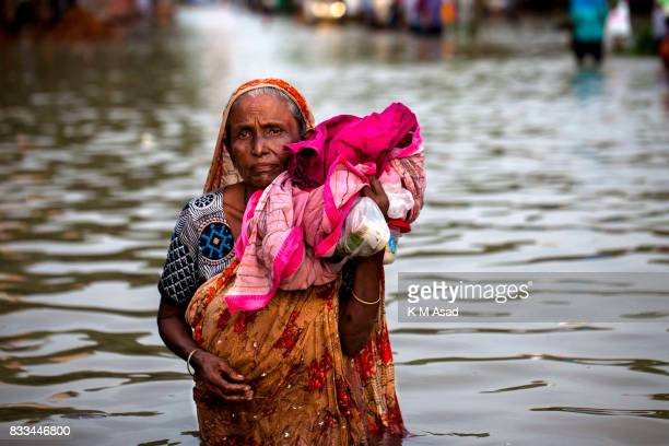 AGRABAD DHAKA CHITTAGONG BANGLADESH An elderly woman wading through a flooded area of Chittagong People traveling in flooded areas in Chittagong...