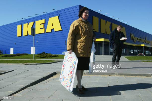 An elderly woman waits with her purchases for a bus outside an IKEA home furnishings store, on April 14, 2004 in Cracow, Poland. Poland is scheduled...
