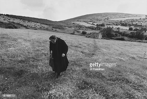 An elderly woman walks across fields into town Tipperary Ireland 1974