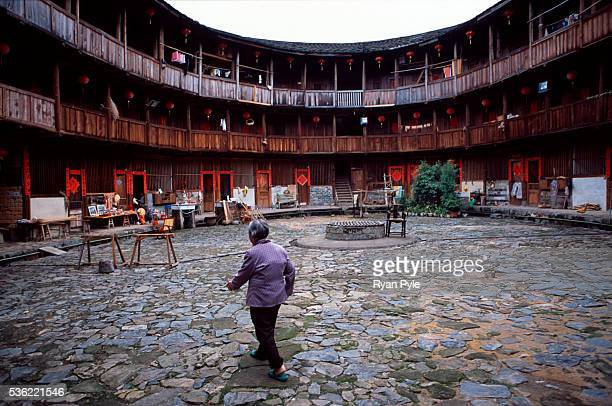 An elderly woman walks across the inner courtyard in a traditional Hakka Tulou home in the county of Yongding, well known as the Hakka Tulou region....
