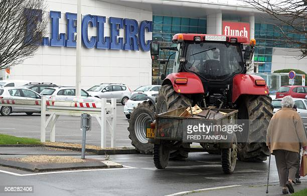 An elderly woman walks by a truck blocking the access to an ELeclerc supermarket in Vannes western France as farmers block the entrance to the...