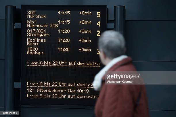 An elderly woman walks by an info sign showing change of bus connections at Hanover Central Trainstation on November 14 2014 in Hanover Germany The...