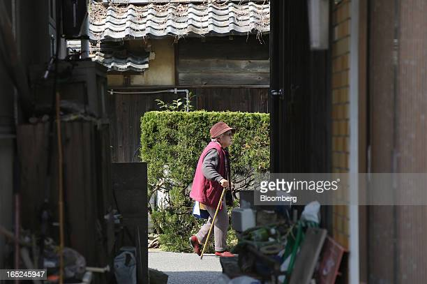 An elderly woman walks down a lane between houses on Gogo Island in Matsuyama Ehime Prefecture Japan on Friday March 22 2013 A combination of the...