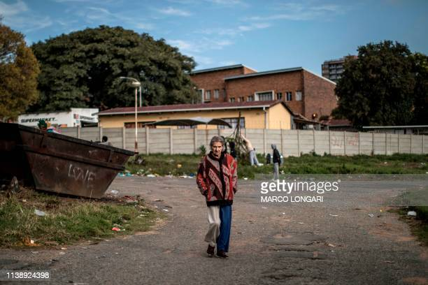 An elderly woman walks in the streets of Johannesburg on April 23 2019 during a protest against the lack of service delivery or basic necessities...