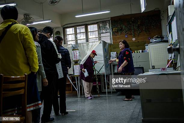 An elderly woman walks out of a booth after casting her vote at a polling station on January 16 2016 in Taipei Taiwan Voters in Taiwan are set to...