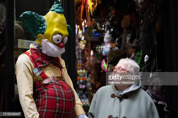 An elderly woman walks passed a Simpsons character in a surgical face mask outside a fancy dress shop on March 18, 2020 in Cardiff, United Kingdom....