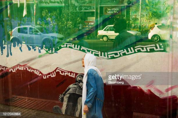 An elderly woman walks past a political wall mural outside the former US embassy in Tehran Iran on Sunday Aug 5 2018 Irans central bank acting on the...