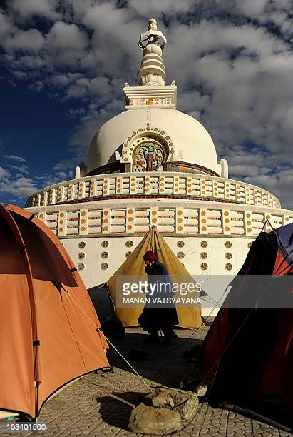 An elderly woman walks past a tent set up by local residents at the Buddhist Shanti Stupa in Leh on August 9 2010The death toll from flash floods in...