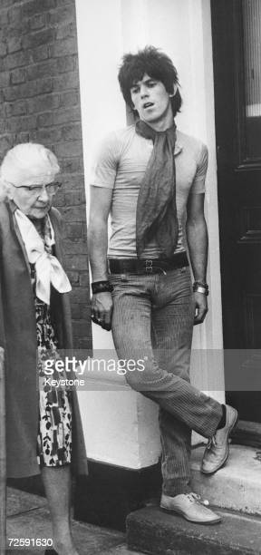 An elderly woman walks past Rolling Stones guitarist Keith Richards at Redlands his Sussex home 28th June 1967 He is on bail pending sentence on drug...