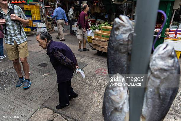 An elderly woman walks past salted fish hanging out to dry on a street signpost near Graham Street the site of one of the oldest wet markets in Hong...