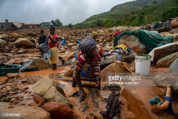 TOPSHOT An elderly woman washes her belongings in the mud on March 19 in Chimanimani on March 19 after the area was hit by the Cyclone Idai More than...